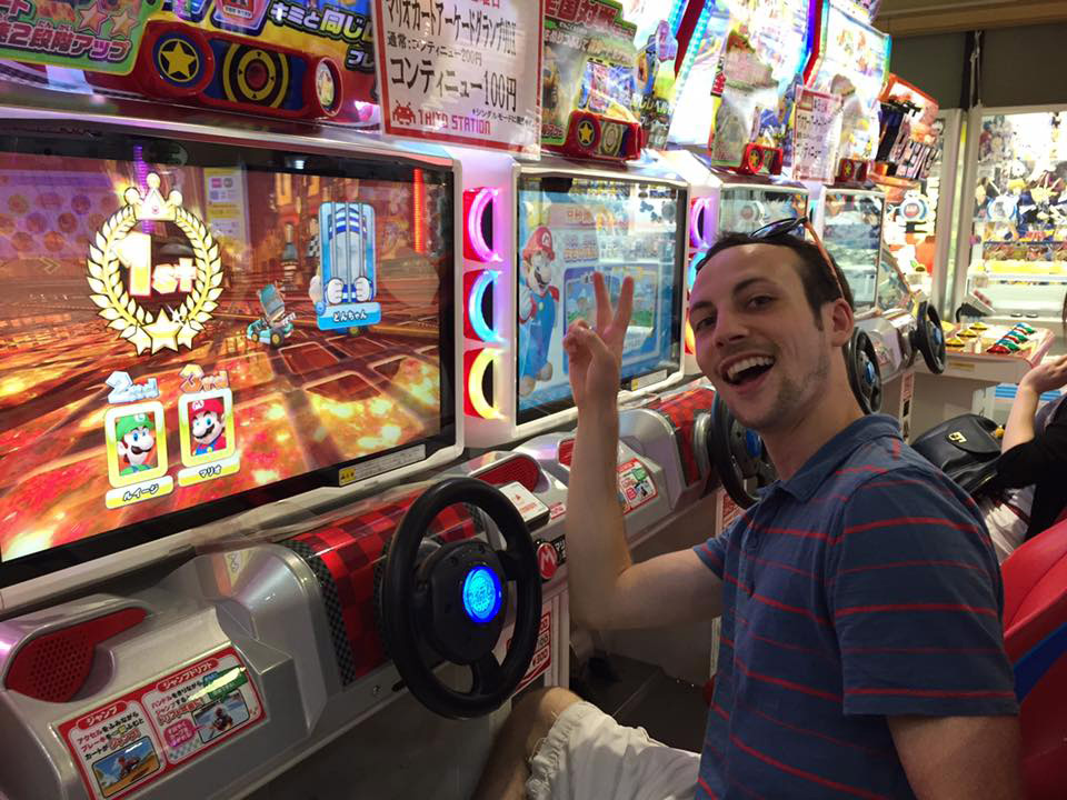 The author is pleased with himself after winning a game of Mario Kart in a Japanese arcade.