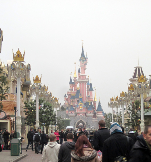 A road stretching towards a Disney castle in the distance